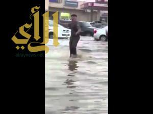 رجل أمن يتحدى غزارة الأمطار لتنظيم حركة السير