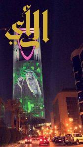 برج المملكة يتزين باللون الأخضر وصورتي خادم الحرمين وولي عهده